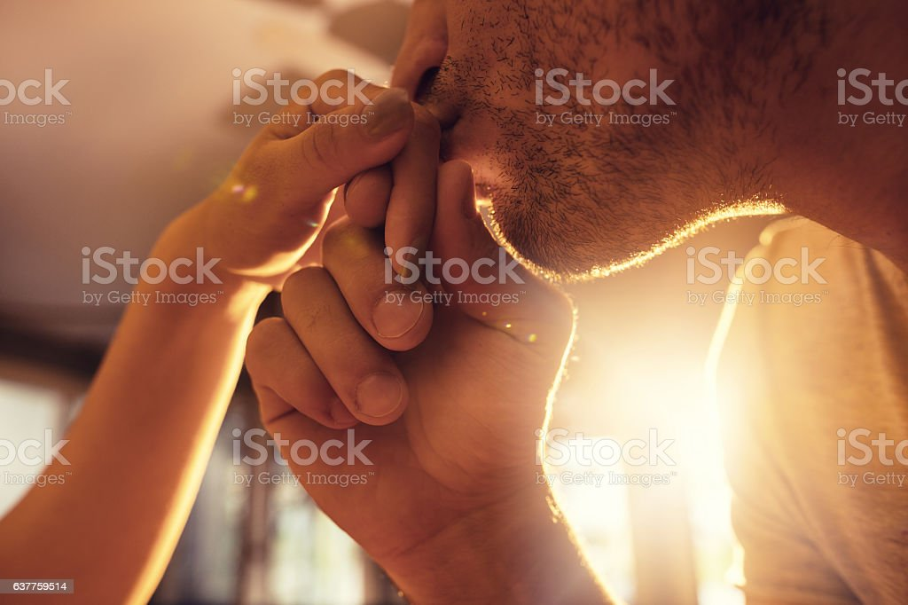 Close up of a man kissing girlfriend's hand. stock photo