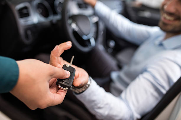 Close up of a man receiving new car key. Close up of a man sitting in a car and receiving car keys from unrecognizable person. car salesperson stock pictures, royalty-free photos & images