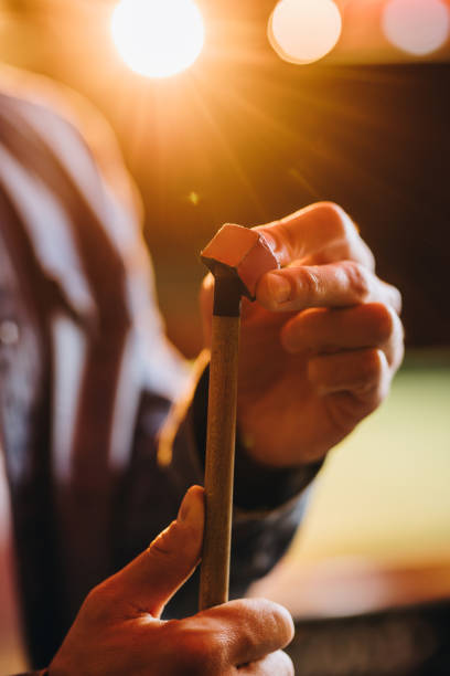 close up of a man rubbing a pool cue with a chalk. - pool cue stock photos and pictures