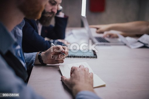 881542122istockphoto Close up of a man taking notes on a business meeting 956458596