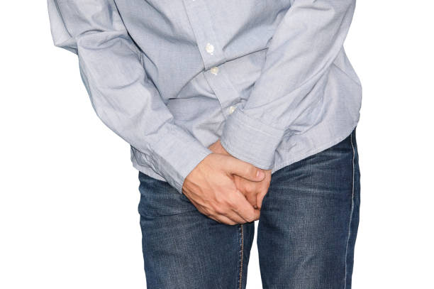Close up of a man with hands holding his crotch, isolated in white Close up of a man with hands holding his crotch, isolated in white. Urinary incontinence. Disease for men. Men's health. Dick stock pictures, royalty-free photos & images