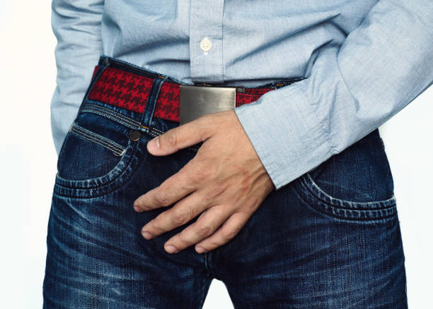Close up of a man with hands holding his crotch Close up of a man with hands holding his crotch, isolated on a white background Dick stock pictures, royalty-free photos & images