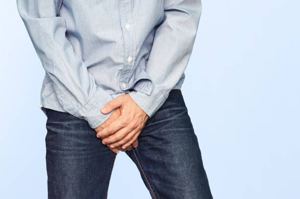 Close up of a man with hands holding his crotch stock photo