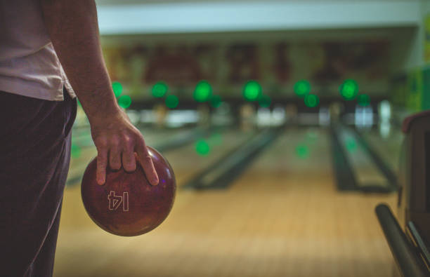 A close up of a man's hand holding bowling ball stock photo