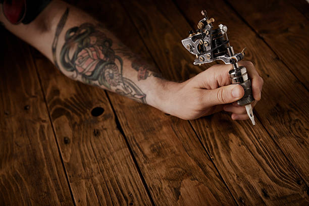 Close up of a man's hand with  tattoo gun stock photo