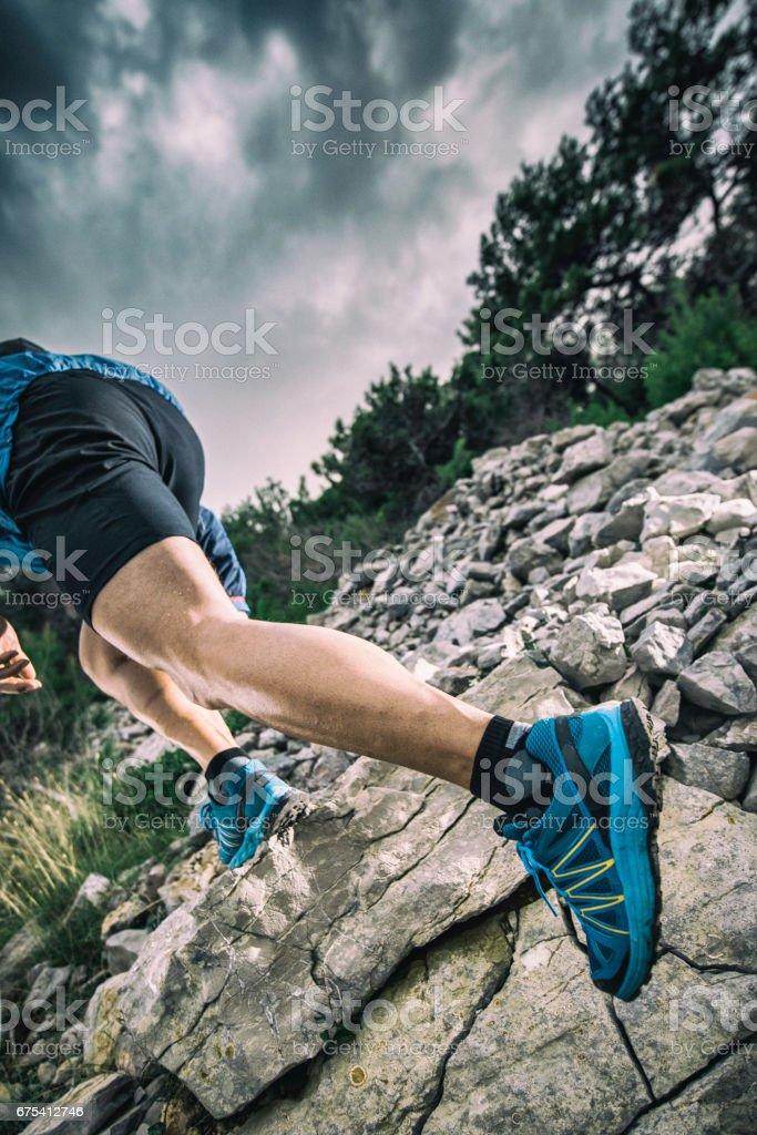 Gros plan de la jambe de l'homme lors de l'exécution d'une colline rocheuse photo libre de droits