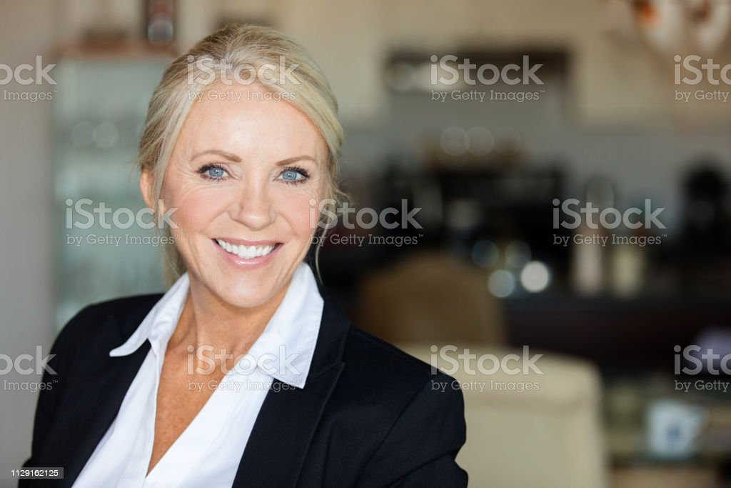 Close up of a mature lawyer smiling Close up of a mature lawyer smiling. She is calm, standing on a coffee shop 40-49 Years Stock Photo