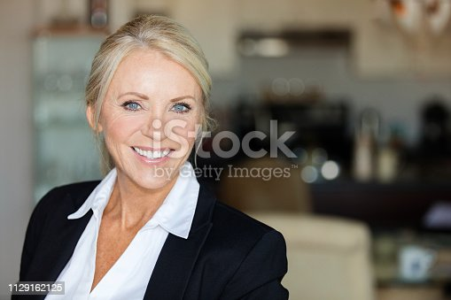 Close up of a mature lawyer smiling. She is calm, standing on a coffee shop