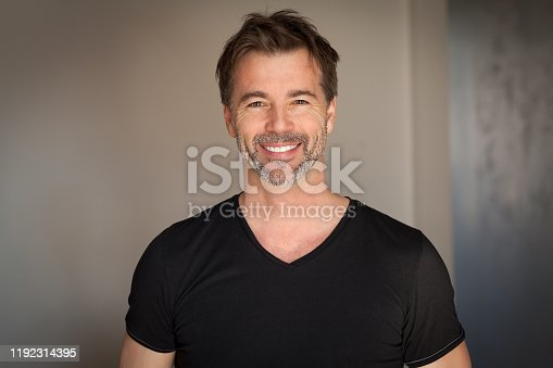 637538262istockphoto Close up Of A Mature Man Smiling At The Camera. Casual black t-shirt. Happy man 1192314395