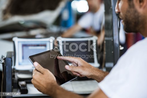 1137474295 istock photo Close up of a mechanic using touchpad in auto repair shop. 1198227082