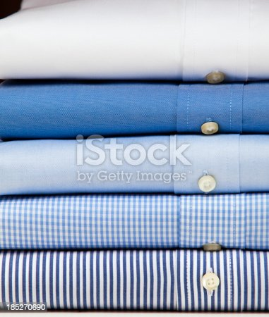 Business shirt button down clothing stacked in a pile