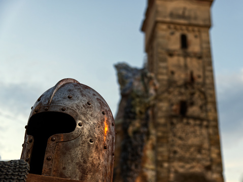 close up of a middleage helmet with a Romanesque bell tower in the background