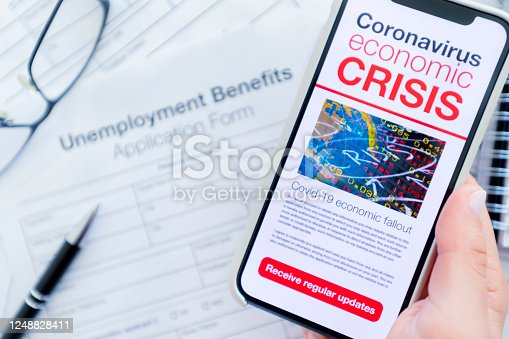 1217929357 istock photo Close up of a mobile phone with Coronavirus covid-19 economic crisis news article. There is an unemployment benefits claim  form in the background on the desk. 1248828411