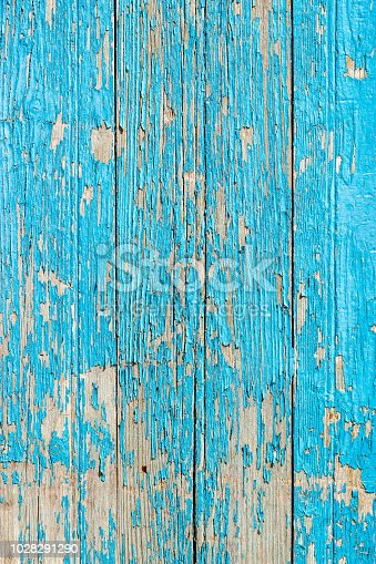 Close up of a old wooden door, teal blue paint peeling off; texture background