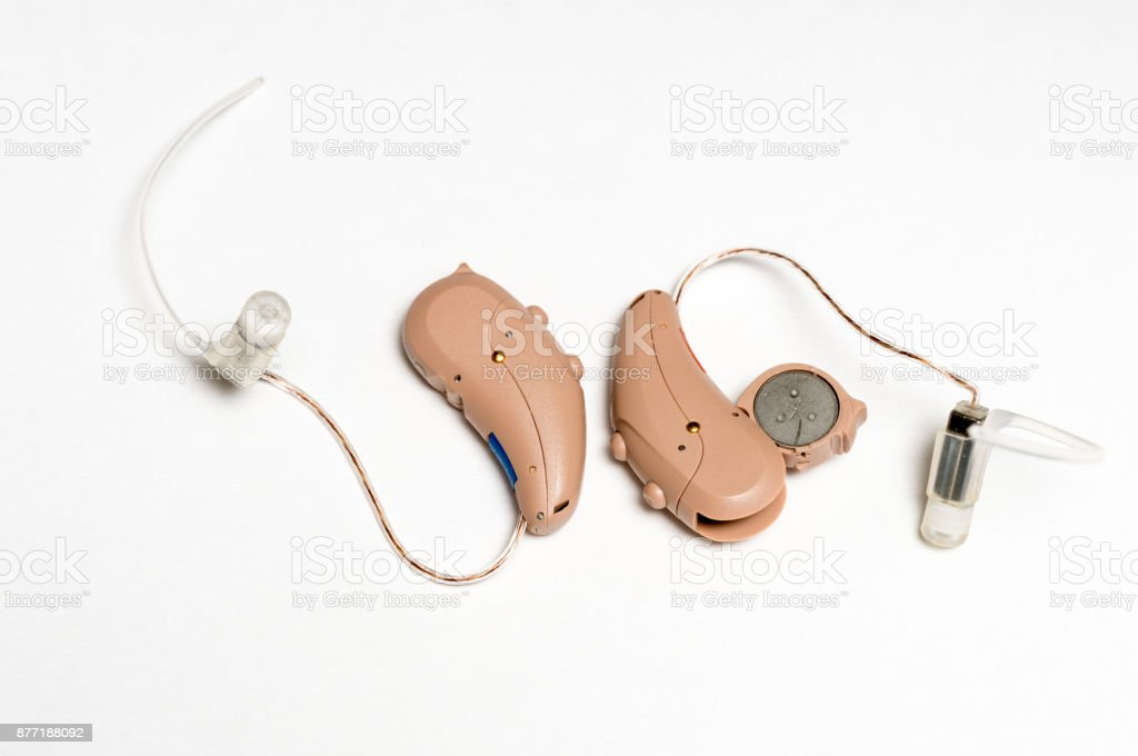 Close up of a pair of tiny modern hearing aids on white background stock photo