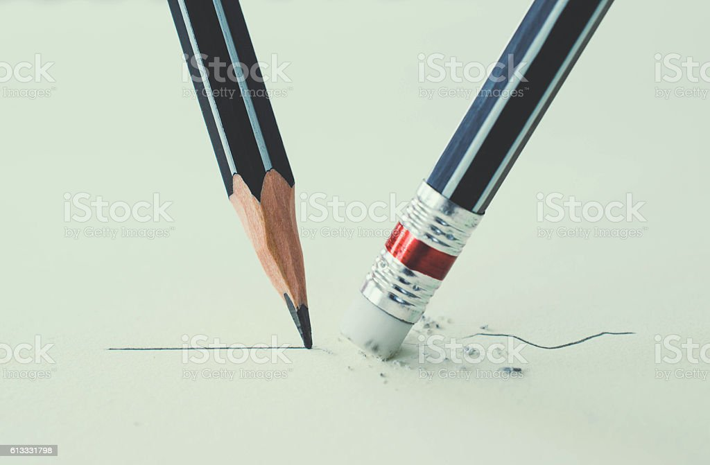 Close up of a pencil eraser removing a crooked line stock photo