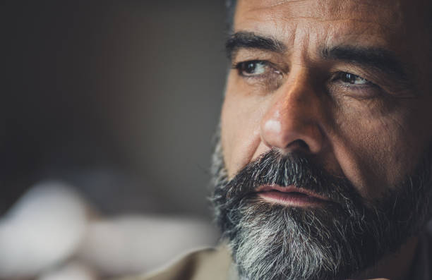 Close up of a pensive mature man looking away. Close up of a bearded senior man thinking of something. introspection stock pictures, royalty-free photos & images