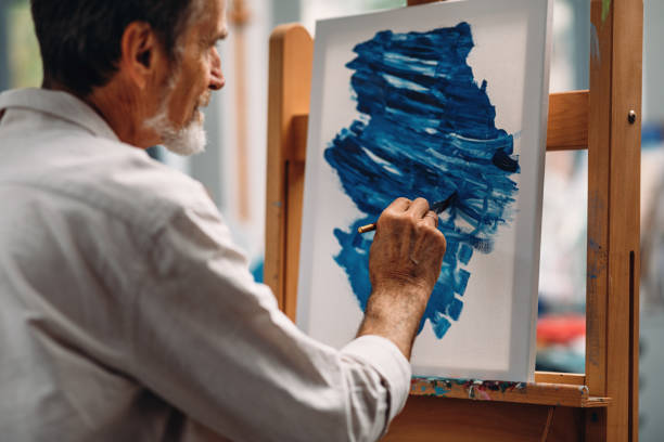 Close up of a pensive mature painter holds a paintbrush looking at a picture on the easel stock photo