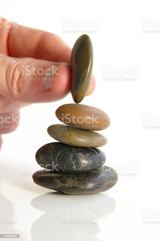 Close up of a person balancing a small stone on top of pile royalty-free stock photo