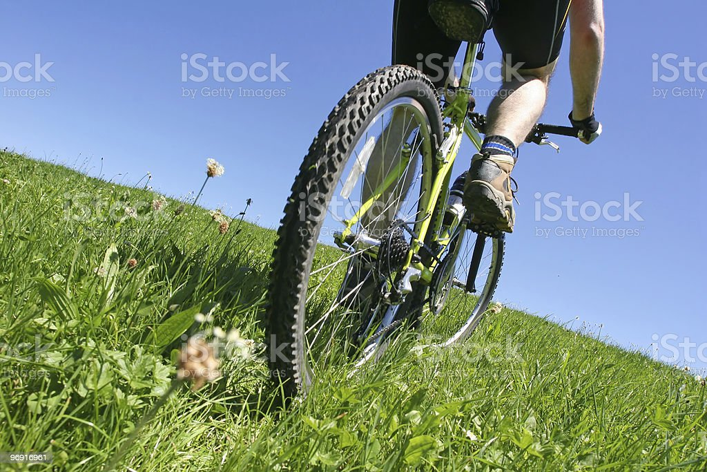 Close up of a person biking up a grassy hill stock photo