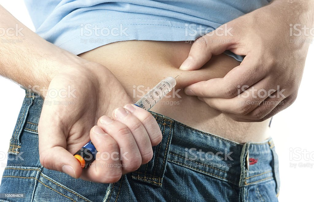 Close up of a person injecting insulin into their stomach stock photo