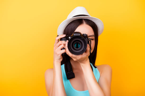 Close up of a photographer making a shot on a digital camera during vacation. She is wearing summer casual outfit and a hat, on bright yellow background stock photo