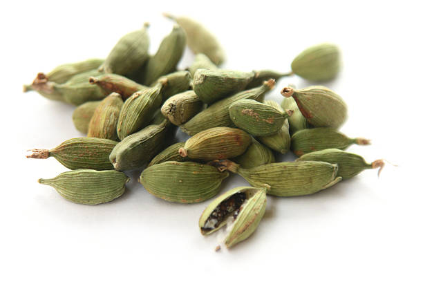 Close up of a pile of cardamom pods Isolated cardamon pods on white background cardamom stock pictures, royalty-free photos & images