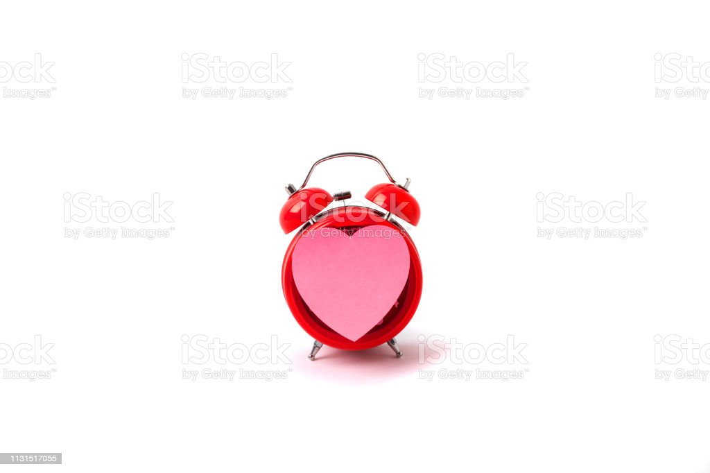 Close up of a Pink heart shaped post-it and Alarm clock stock photo