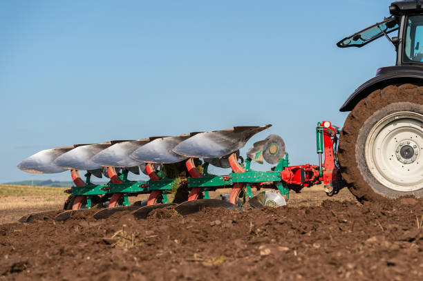 Close up of a plough attached to a tractor being used in a field in Dumfries and Galloway south west Scotland A plough being used in late summer to prepare a field and make it ready to sow a new crop to harvest next year johnfscott stock pictures, royalty-free photos & images