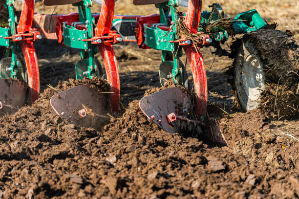 Close up of a plough being used in a field in Dumfries and Gallowy south west Scotland A field being ploughed to prepare it for sowing seed for next years harvest johnfscott stock pictures, royalty-free photos & images