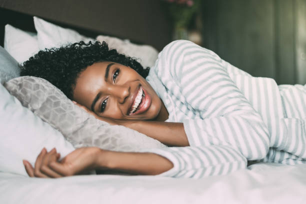 close up of a pretty black woman with curly hair smiling and lying on bed looking at the camera stock photo