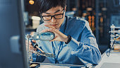 istock Close Up of a Professional Japanese Electronics Development Engineer in Blue Shirt Soldering a Circuit Board in a High Tech Research Laboratory with Modern Computer Equipment. 1193074386