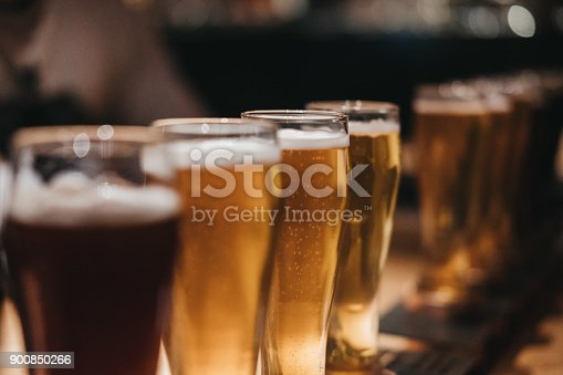 istock Close up of a rack of different kinds of beers, dark to light, on a table. 900850266