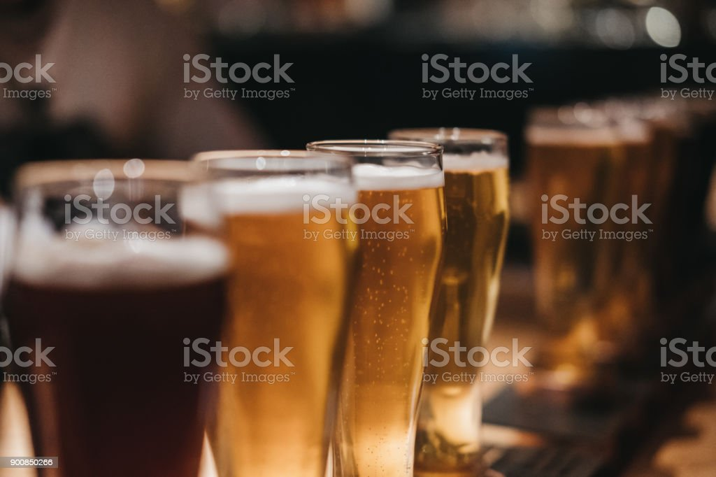 Close up of a rack of different kinds of beers, dark to light, on a table. stock photo