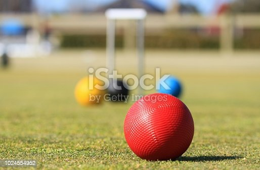 The focus is on a single red croquet ball in the foreground on a green lawn with a defocused group of colored croquet balls and a hoop in the background