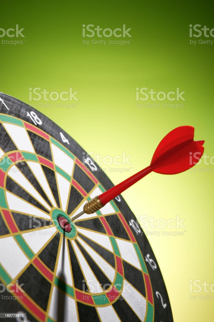 Close up of a red dart in the bullseye of a dart board stock photo