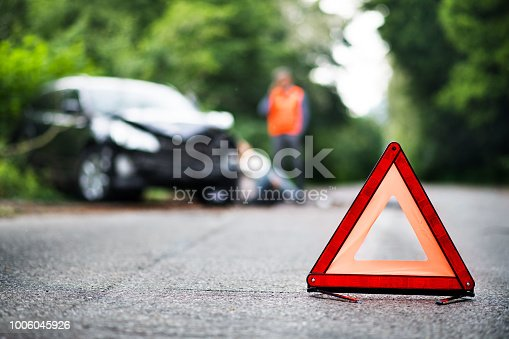 istock A close up of a red emergency triangle on the road in front of a car after an accident. 1006045926