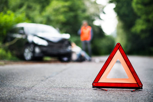 A close up of a red emergency triangle on the road in front of a car after an accident. stock photo