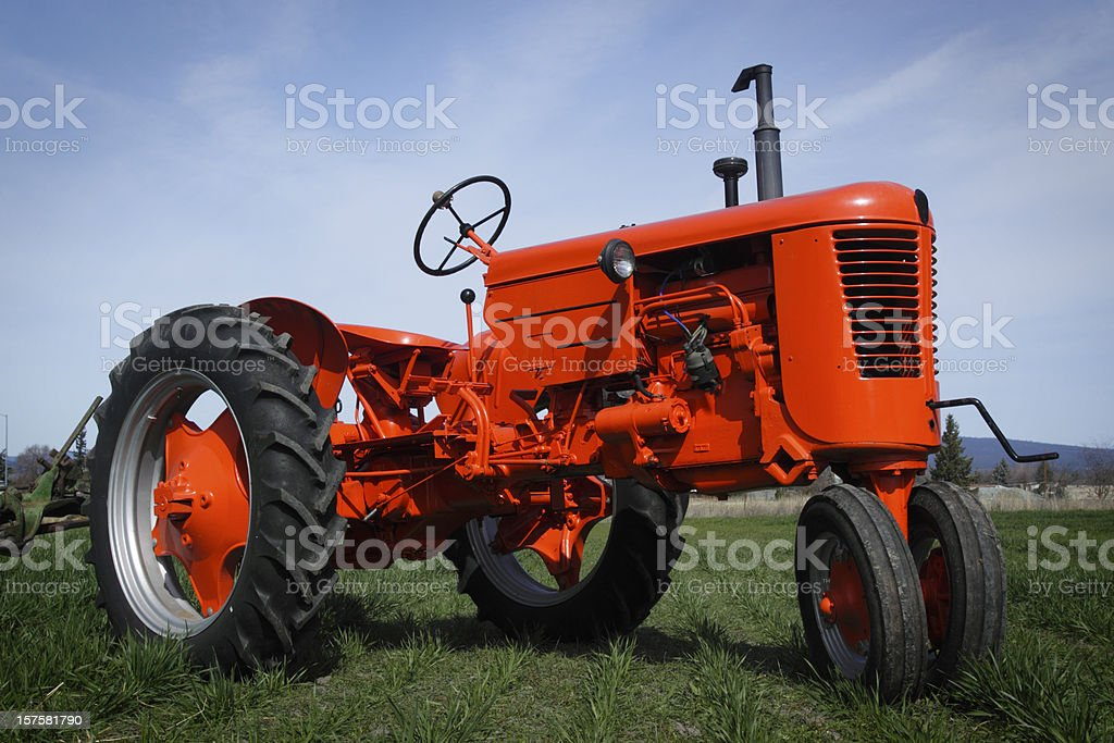 Close up of a red tractor on grass royalty-free stock photo
