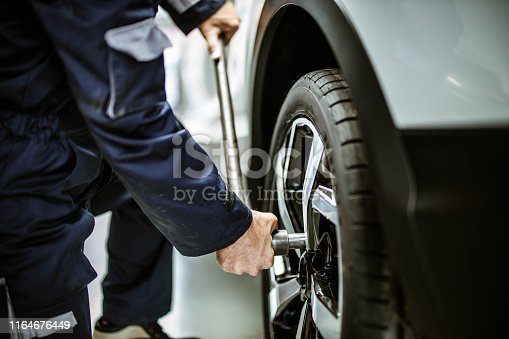 Close up of unrecognizable auto repairman using socket wrench while changing wheel and tire in a workshop.