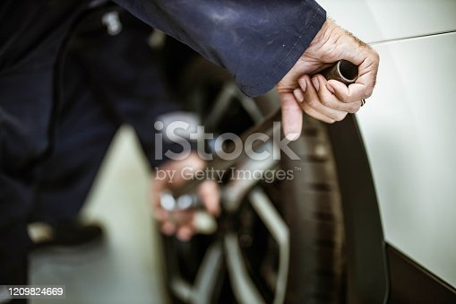 498888104 istock photo Close up of a repairman changing wheel and tire in a workshop. 1209824669