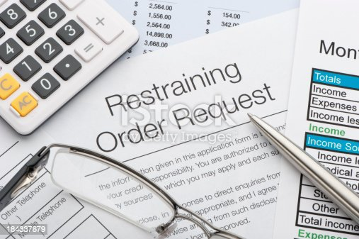 Close up of a restraining order request with pen and calculator
