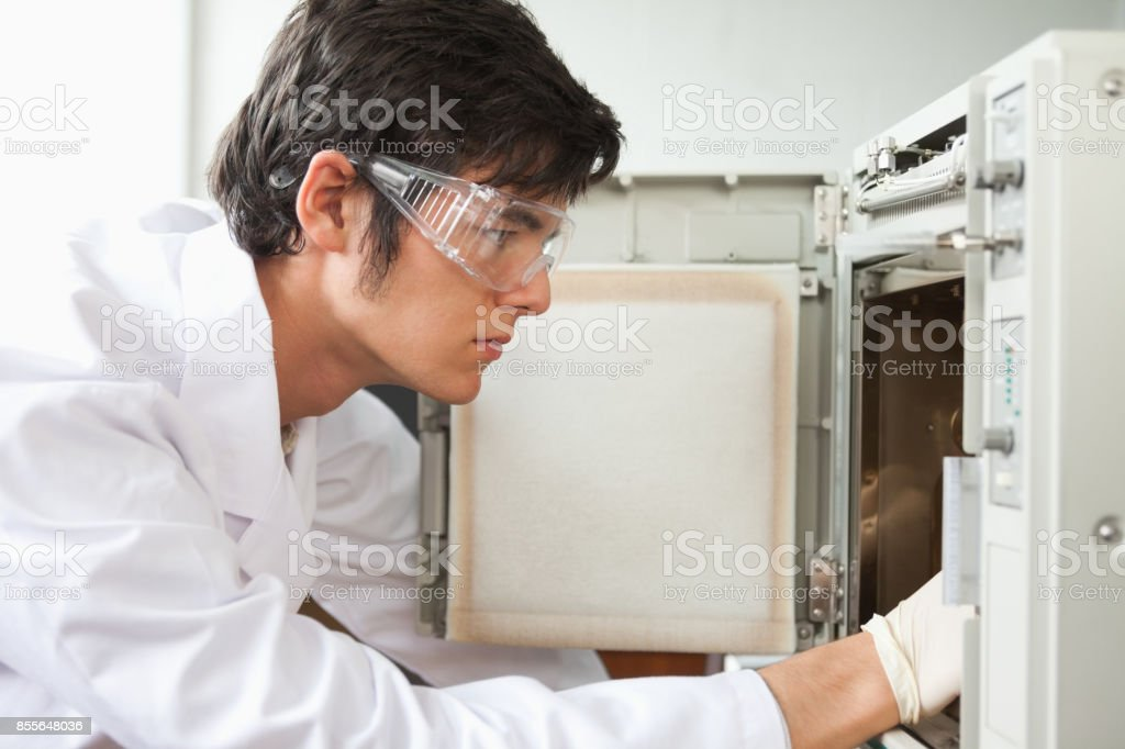 Close up of a scientist using a laboratory chamber furnace stock photo