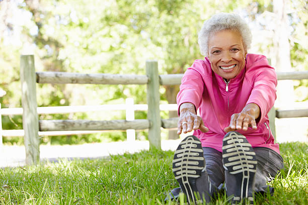 Close up of a senior woman stretching in the park  Senior African American Woman Exercising In Park Stretching To Tough Her Toes touching toes stock pictures, royalty-free photos & images