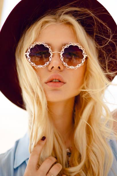 nahaufnahme einer gefühlvollen blondine mit runder blumiger sonnenbrille, großen lippen, gewellten haaren und burgunder hut, mit blick auf kamera. - haarschnitt rundes gesicht stock-fotos und bilder