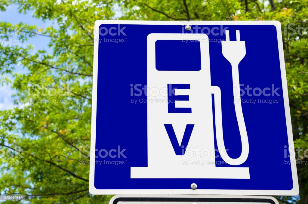 Close up of a Sign indicating an Electric Vehicle Recharging Point Close photo of a Blue Sign indicating an Electric Vehicle Recharging Point. Green Trees are Visible in Background. Ecological Mode of Transport. Alternative Fuel Vehicle Stock Photo