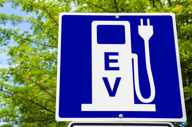 Close up of a Sign indicating an Electric Vehicle Recharging Point Close photo of a Blue Sign indicating an Electric Vehicle Recharging Point. Green Trees are Visible in Background. Ecological Mode of Transport. alternative fuel vehicle stock pictures, royalty-free photos & images