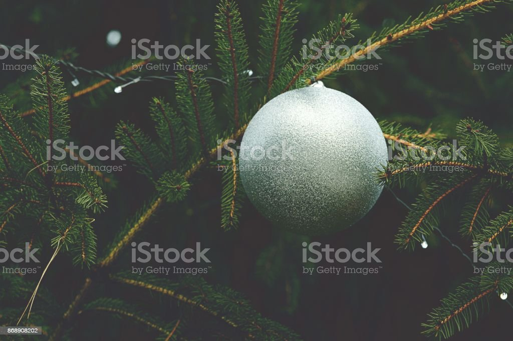 Close up of a silver glittery bauble on a christmas tree - Soft focus stock photo