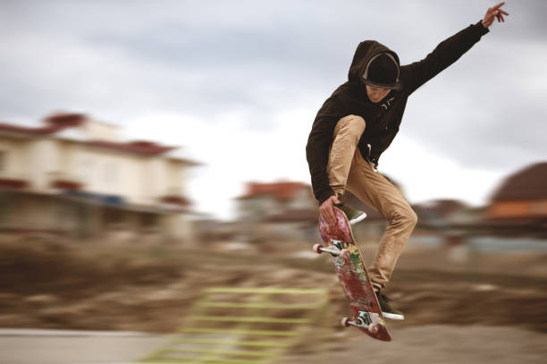 Close up of a skateboarders feet while skating active performance of stunt teenager shot in the air on a skateboard in a skate park stock photo