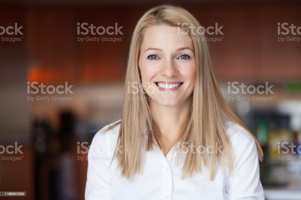 Close up Of A Smiling Caucasien blond woman in the kitchen at the office Close up Of A Smiling Caucasien blond woman in the kitchen at the office 30-39 Years Stock Photo